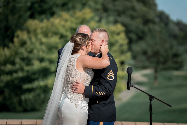 bride and groom kissing in front of pastor after saying their vows during intimate country club wedding outdoors