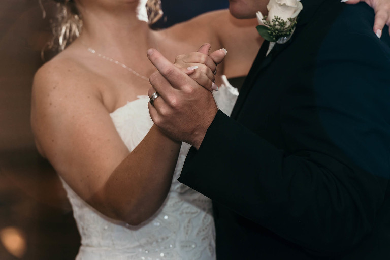 Close up of bride and groom holding hands during First Dance at their intimate country club wedding