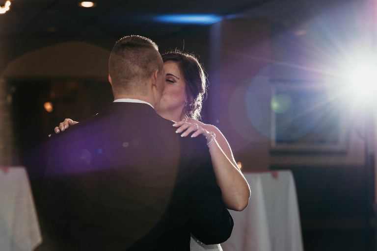 bride and groom kiss during first dance at intimate country club wedding