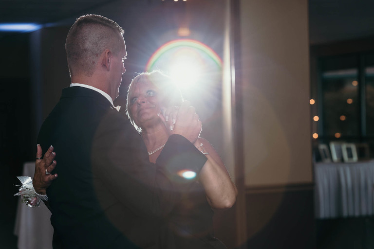 Mother of groom looking at her son during mother-son dance at intimate country club wedding