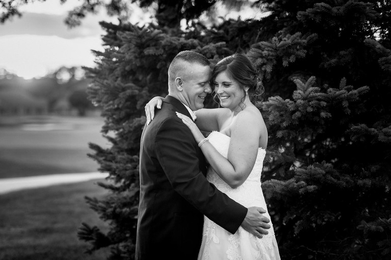 Black and white photo of bride and groom embracing and smiling while standing in front of a pine tree on golf course during intimate country club wedding