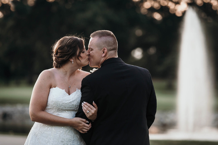 Bride and groom kissing on golf course at sunset during intimate country club wedding in Fort Wayne, Indiana