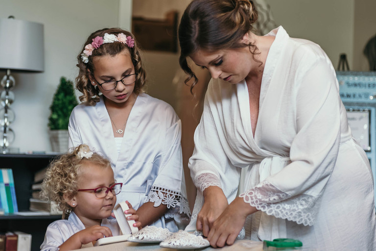 bride standing with young nieces, putting penny in her shoe for good luck during bridal prep prior to the start of her intimate country club wedding