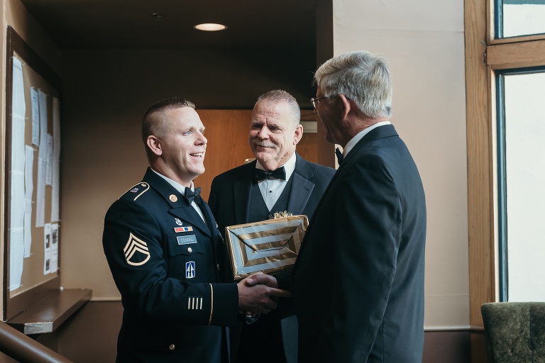 groom standing with father and shaking father-in-law's hand