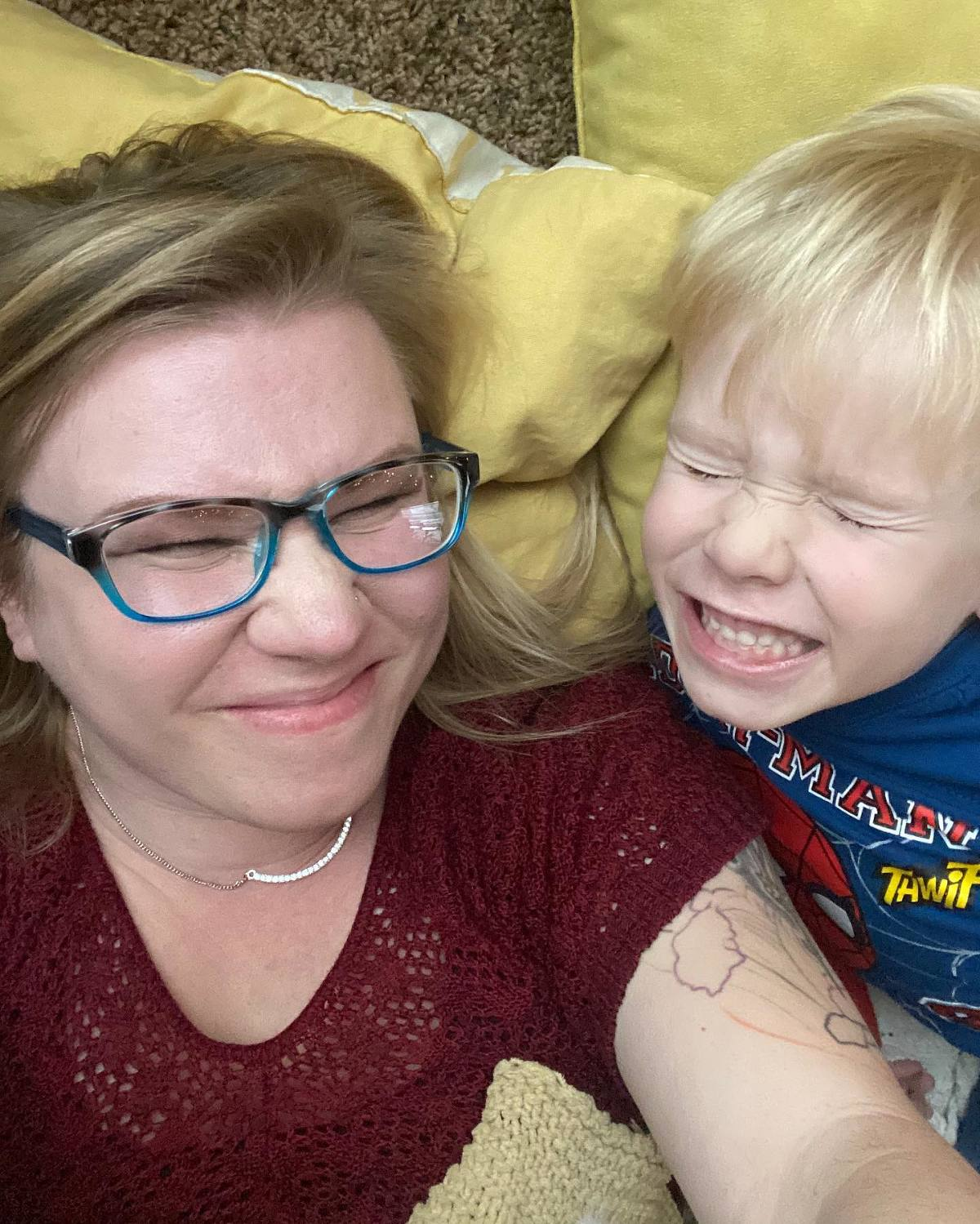 Blonde mother and young blonde son squinting and smiling together
