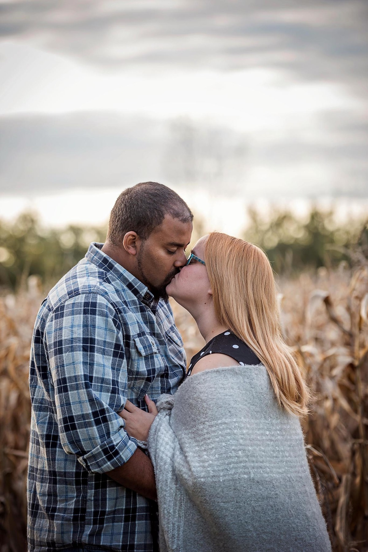 Engaged couple kiss near corn field during fall engagement session at Salomon Farm Park in Fort Wayne, Indiana