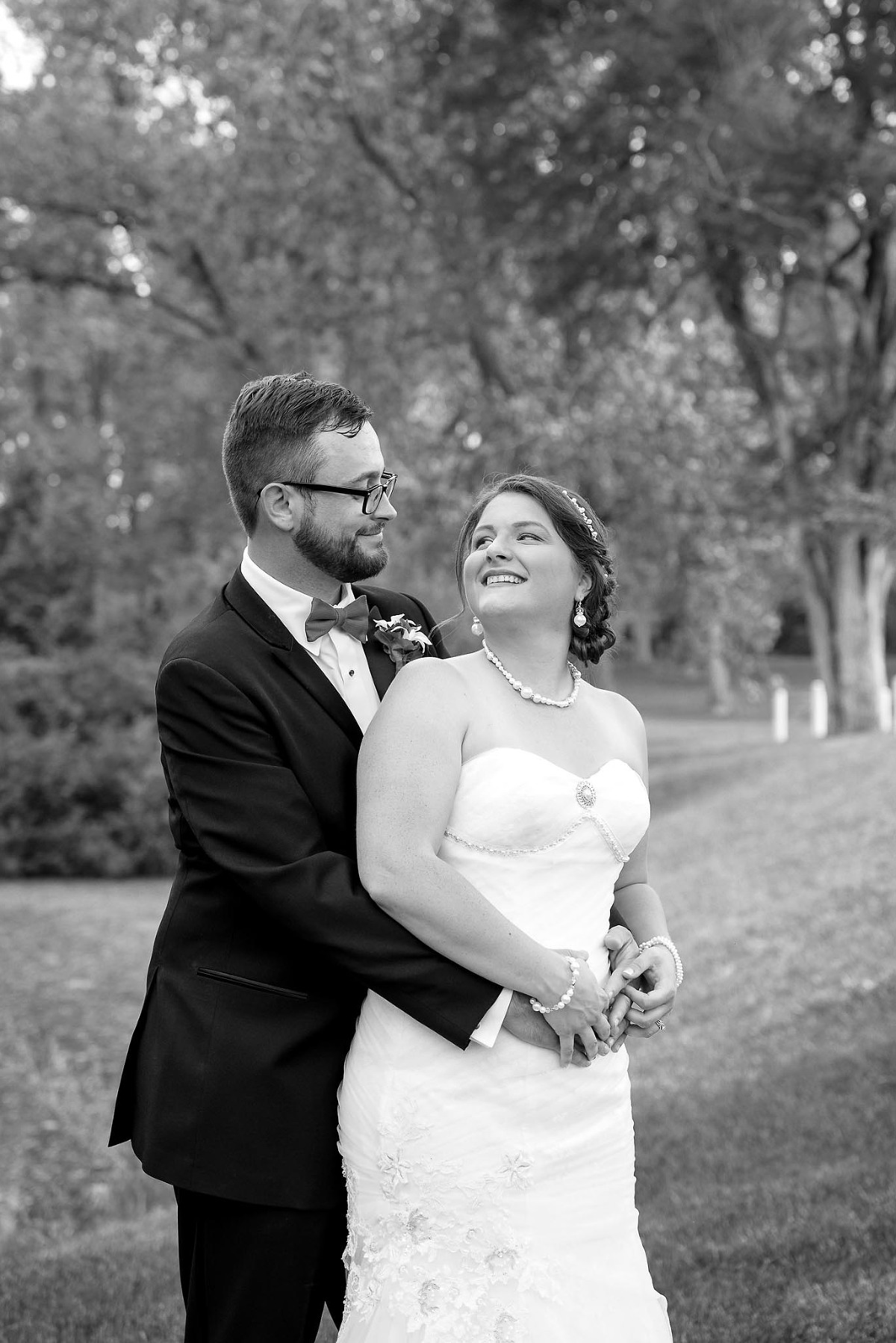 Black and white image of groom embracing bride at romantic outdoor wedding at Park Edelweiss in Fort Wayne, Indiana