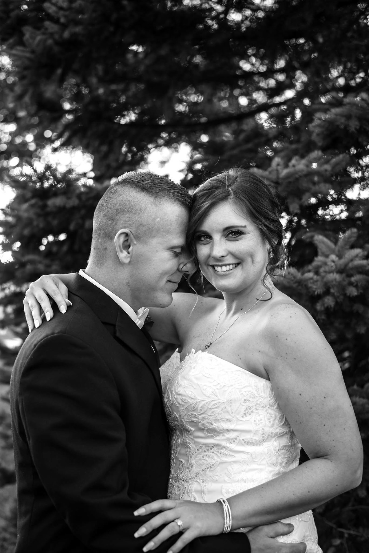 Black and white image of groom nuzzling bride during portrait session near pine trees at their intimate country club wedding at Pine Valley Country Club in Fort Wayne, Indiana
