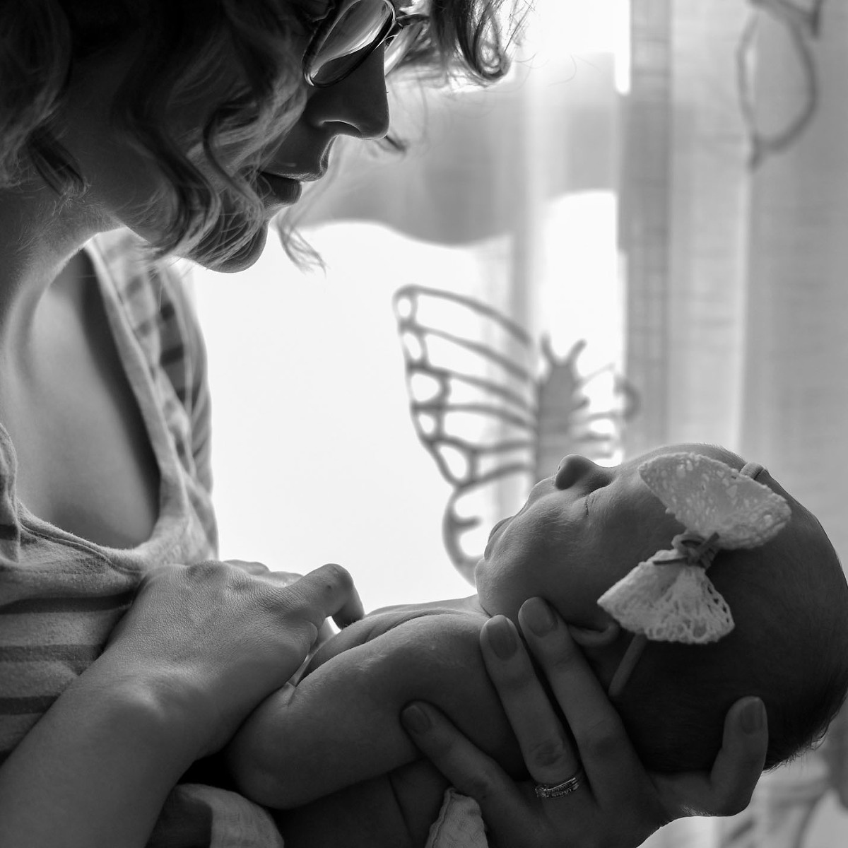 Black and white image of mother looking at sleeping newborn daughter during in home newborn session in Fort Wayne, Indiana