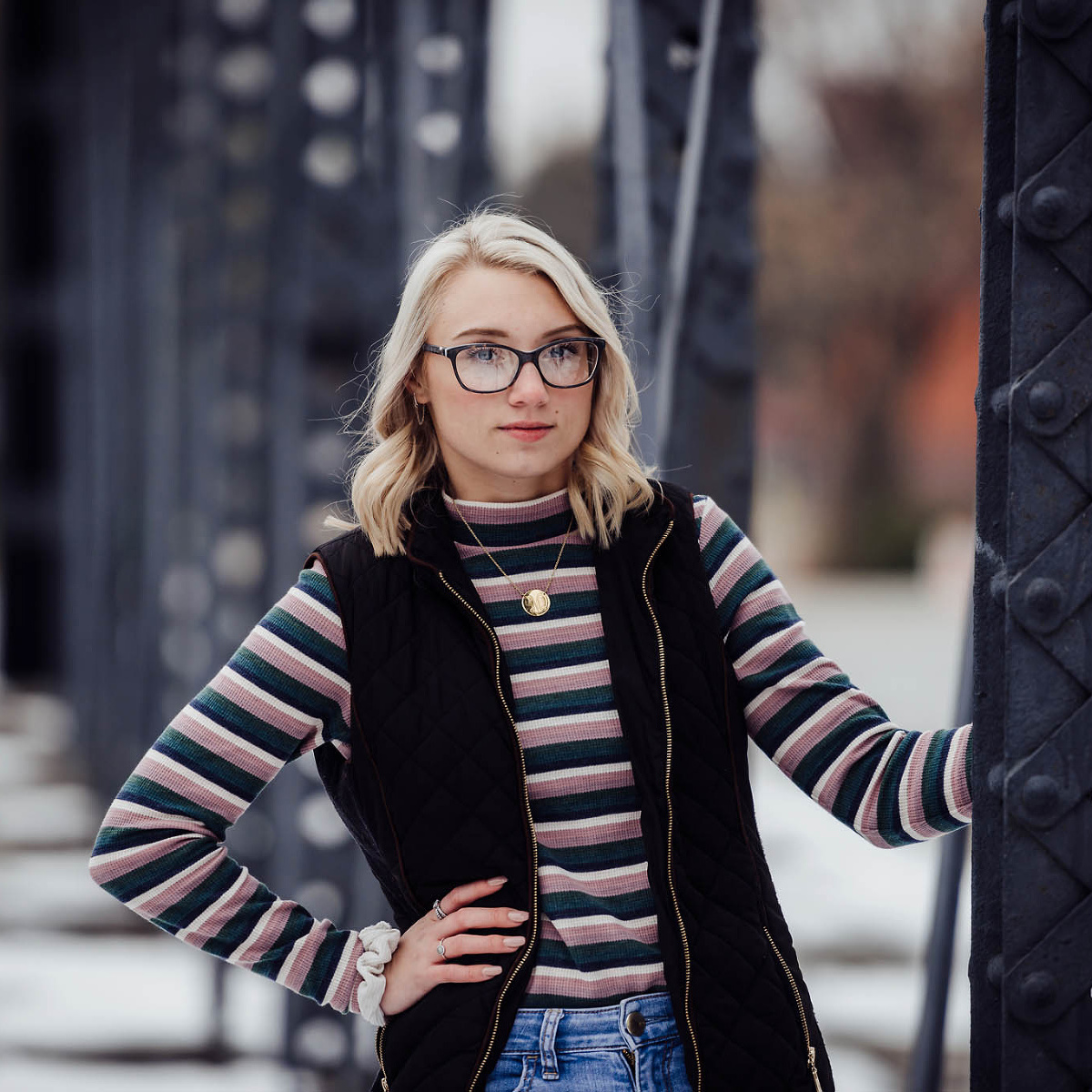 Blonde girl posing on Wells Street Bridge during winter Garrett High School Seniors session in Fort Wayne, Indiana