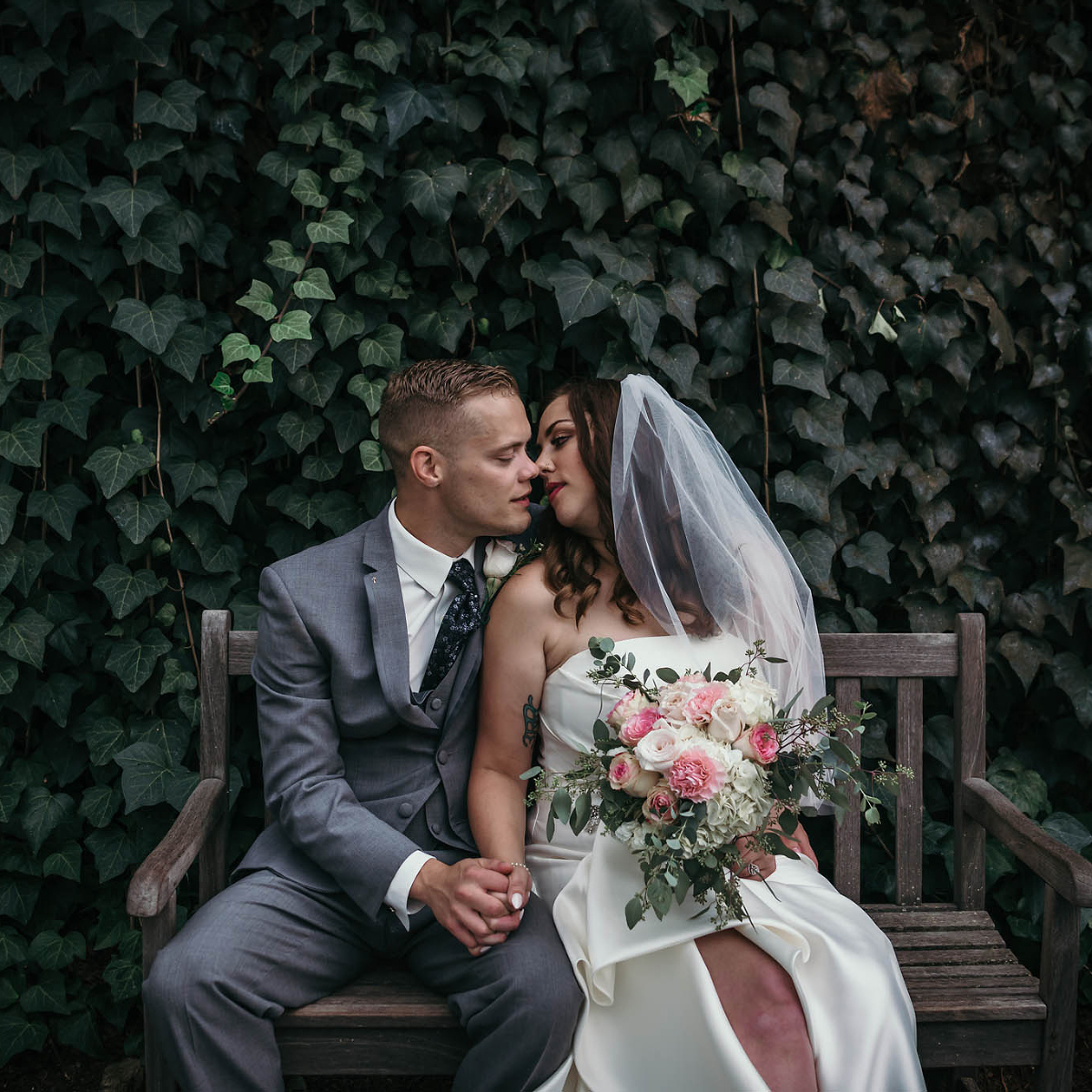 Bride and groom sit on bench together in front of foliage during Art Deco inspired summer wedding at the Foellinger-Freimann Botanical Conservatory in Fort Wayne, Indiana