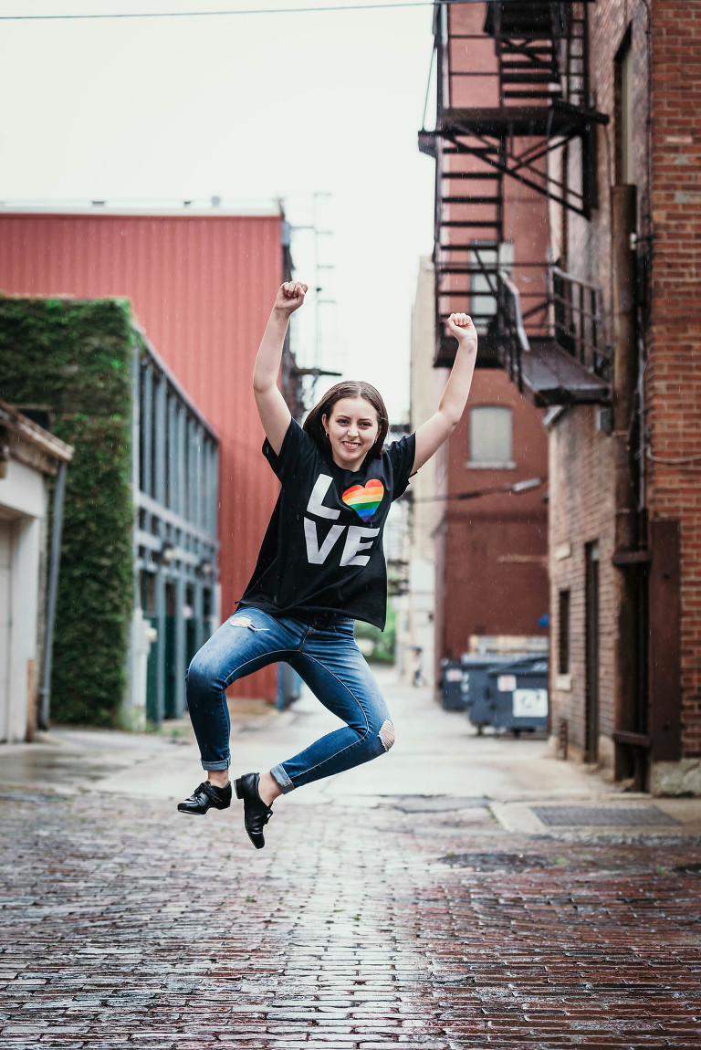 Brunette teenage girl jumping in air and clicking tap shoes together during fun high school seniors session in downtown Fort Wayne, Indiana