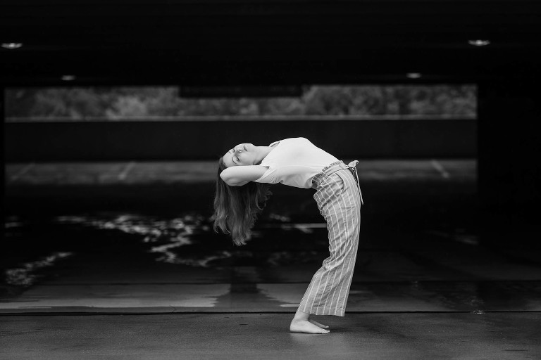 Black and white image of brunette teenage girl in a dance pose on top of parking garage in downtown Fort Wayne, Indiana
