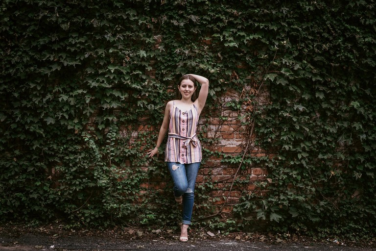 Brunette teenage girl leaning back against ivy and brick wall during fun high school seniors session in downtown Fort Wayne, Indiana