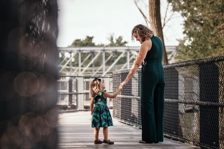 Blonde mother and young daughter holding hands and looking at each other during mama and me mini session at Promenade Park in downtown Fort Wayne, Indiana