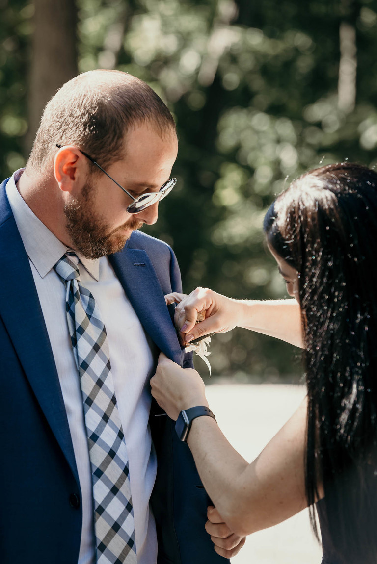 Bridesmaid pinning boutonnière on groom prior to wedding ceremony at Pokagon State Park