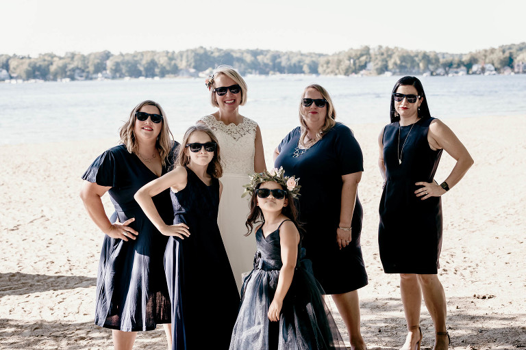 Bridesmaids posing with bride in sunglasses on beach at Pokagon State Park