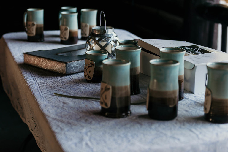 Details of handmade ceramic mugs at unique outdoor DIY wedding reception at Pokagon State Park