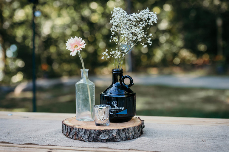 Unique outdoor DIY wedding centerpieces with fresh flowers and jug from Auburn Brewing Company at Pokagon State Park