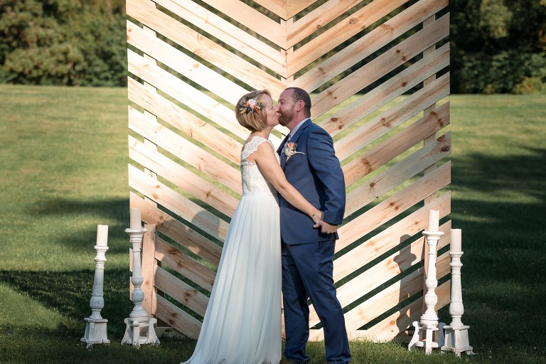 Bride and groom kissing at altar during outdoor wedding ceremony at Pokagon State Park