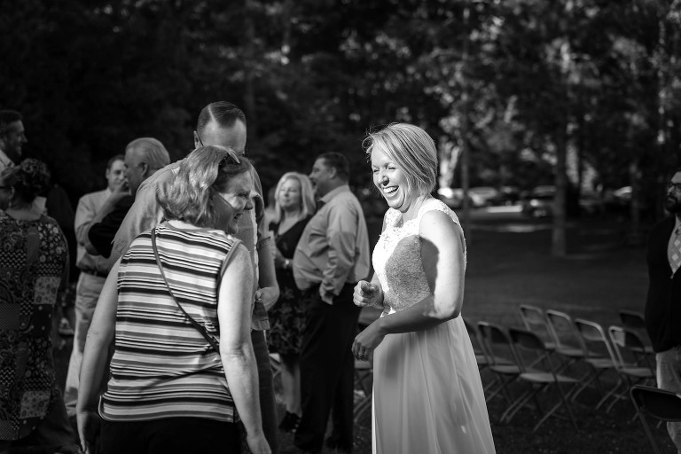 Black and white image of bride smiling at guests after outdoor wedding ceremony at Pokagon State Park