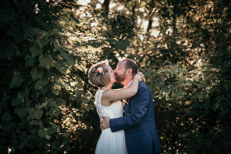 Bride and groom kissing in front of trees after unique outdoor DIY wedding at Pokagon State Park