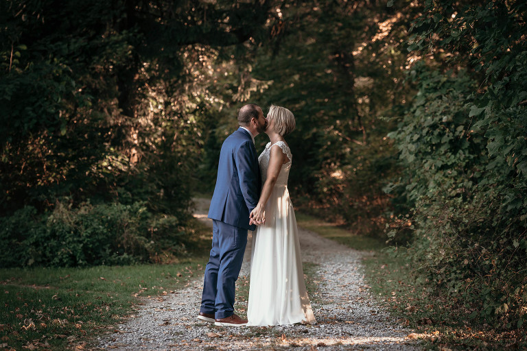 Groom pulling bride in for a kiss while holding hands on a path at Pokagon State Park