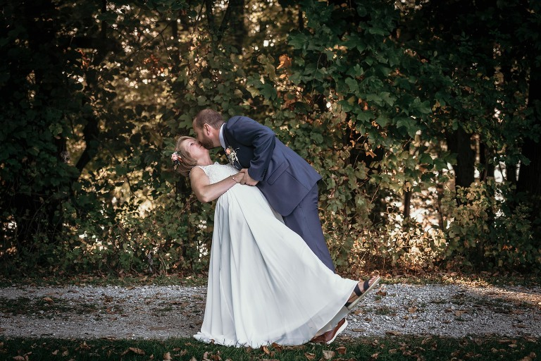 Groom dipping bride and kissing during outdoor portrait session at Pokagon State Park