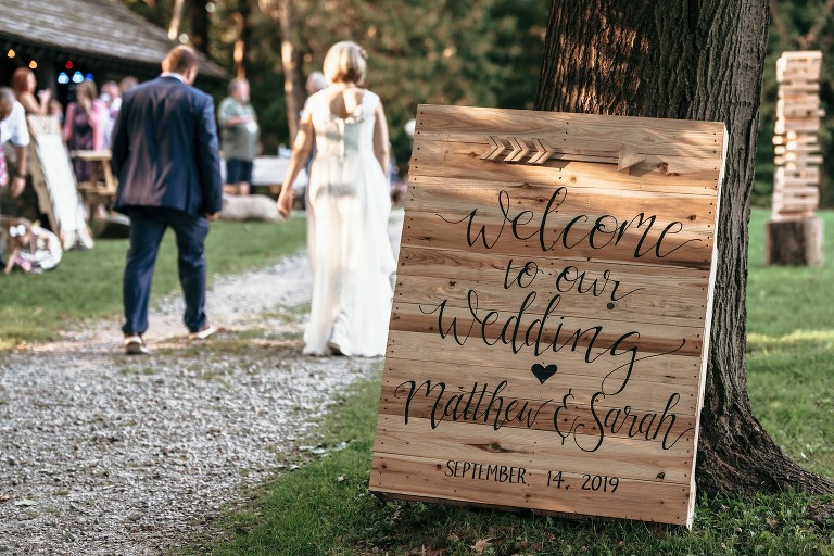 Detail shot of handmade wooden welcome sign for unique outdoor DIY wedding at Pokagon State Park with bride and groom walking in the background