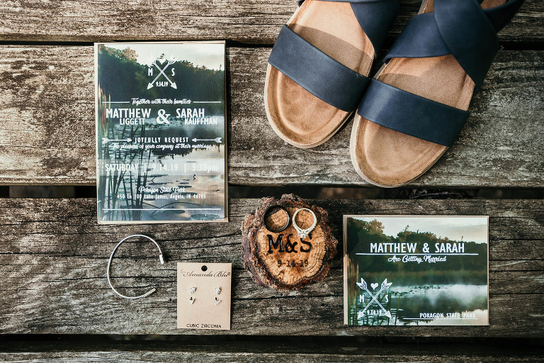 Details of wedding invitation, jewelry, bridal shoes, and wedding rings on picnic table at Pokagon State Park unique outdoor DIY wedding