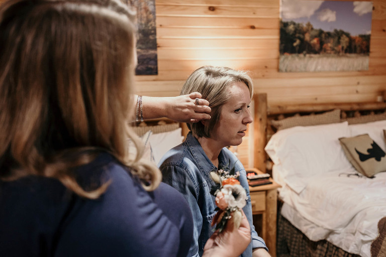 Bridesmaid putting floral hairpiece in blonde bride's hair during bridal prep