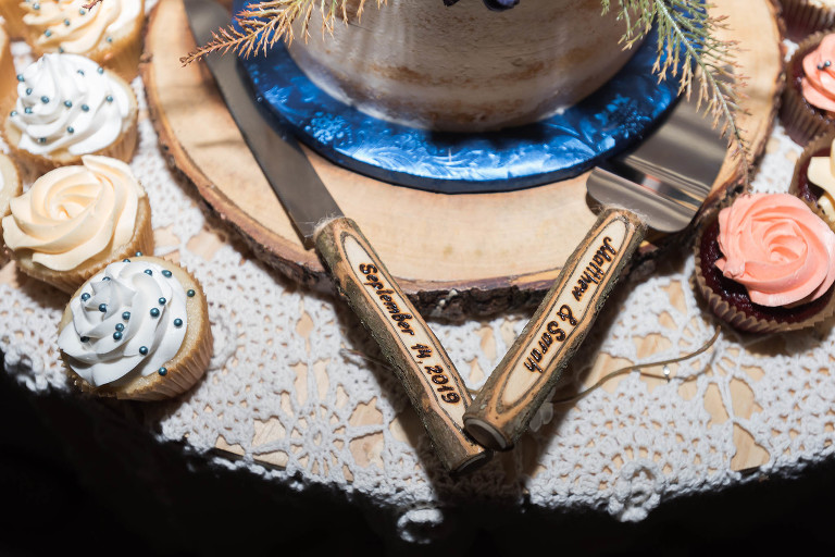 Close up of engraved wooden serving knife and spatula for wedding cake
