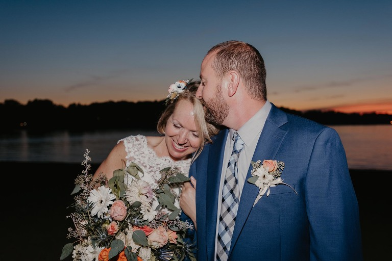 Groom kissing bride's forehead on beach at sunset at Pokagon State Park
