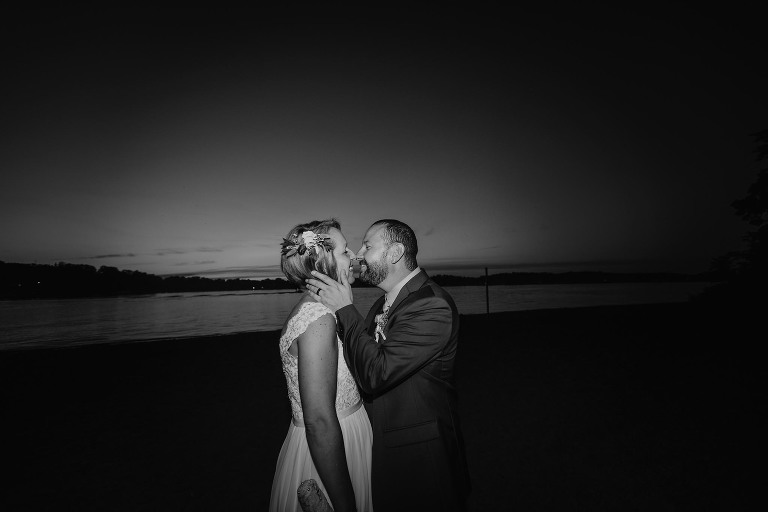Black and white image of groom beginning to kiss bride on beach at sunset at Pokagon State Park
