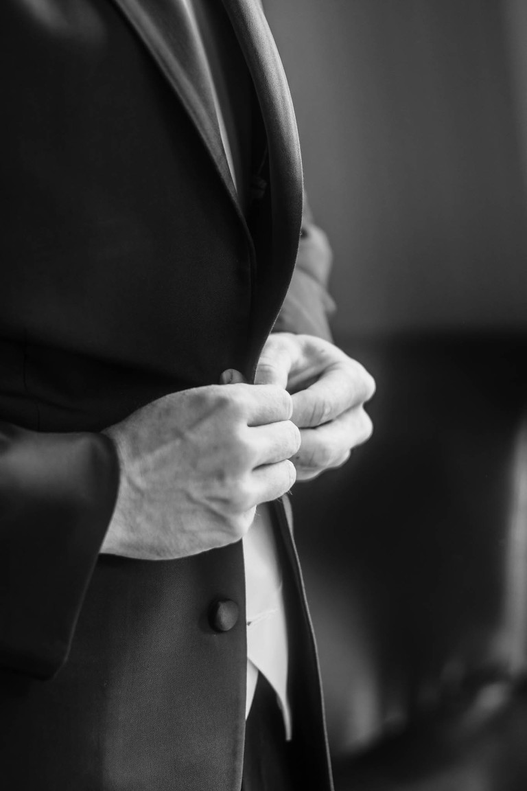 Black and white close up of groom buttoning suit