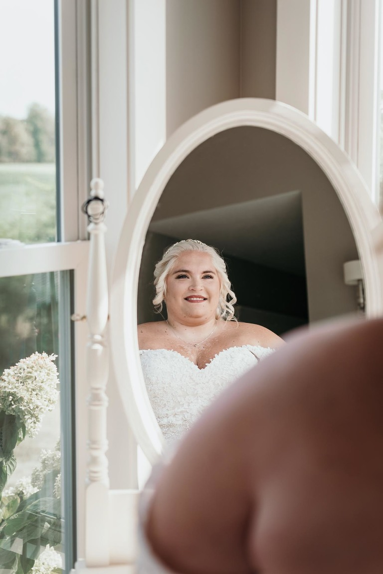 Bride looking at herself in mirror after getting dressed during bridal prep