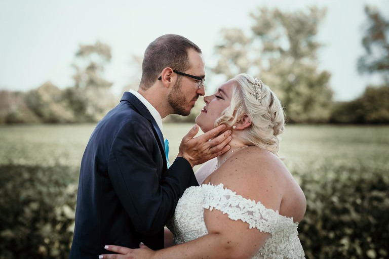 Groom gently lifting bride's chin for a kiss during a photo shoot at intimate fall wedding