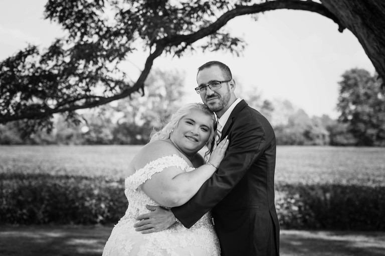 Black and white photo of bride and groom posing in front of field outside