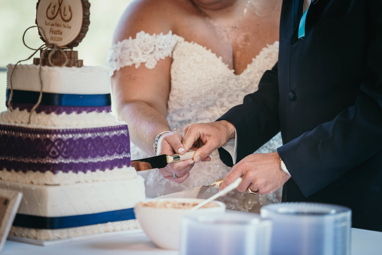 Close up of bride and groom cutting cake during reception at intimate fall wedding at the Lodge at River Valley in Yorktown, Indiana