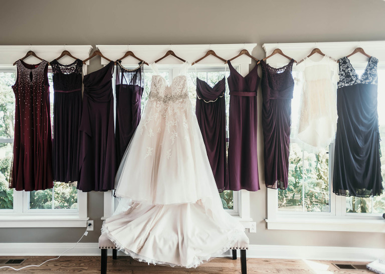 Wedding dress and bridesmaid dresses hanging on window ledge