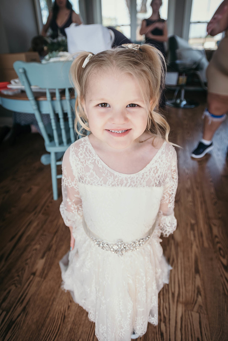 Flower girl smiling for photo at intimate fall wedding at the Lodge at River Valley in Yorktown, Indiana