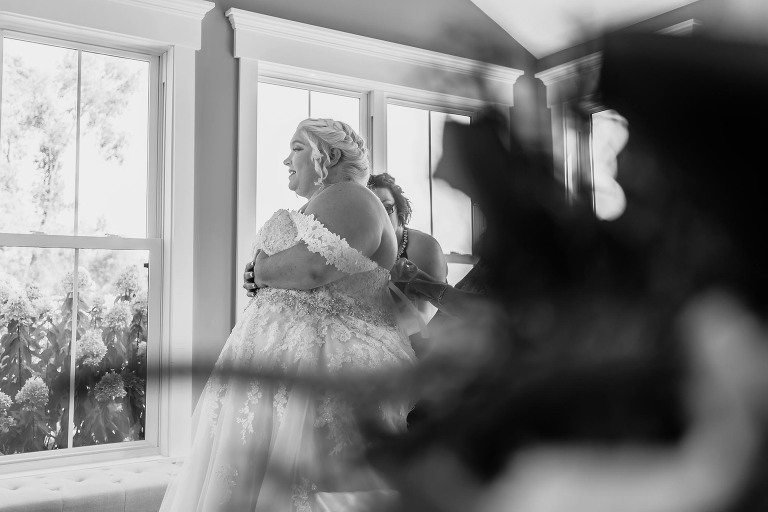 Black and white photo of bride standing still while being laced into dress during intimate fall wedding at the Lodge at River Valley in Yorktown, Indiana