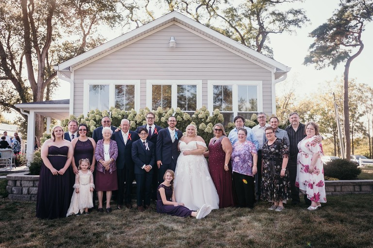 Large group family photo during outside intimate fall wedding at the Lodge at River Valley in Yorktown, Indiana