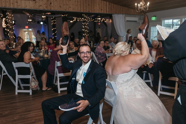 Bride and groom playing the shoe game during reception at intimate fall wedding at the Lodge at River Valley in Yorktown, Indiana