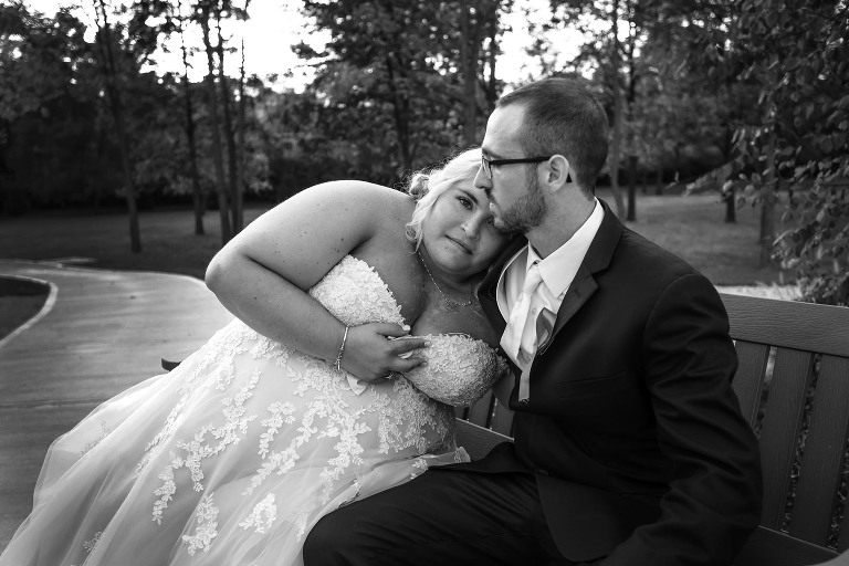 Black and white image of bride resting her head on groom's shoulder while sitting on a bench during a quiet moment at intimate fall wedding at the Lodge at River Valley in Yorktown, Indiana