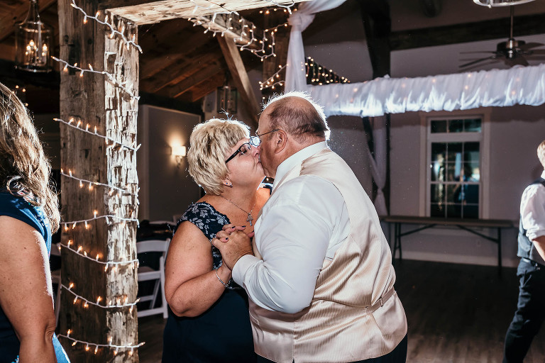Mother and father of groom dancing and kissing during reception of intimate fall wedding at the Lodge at River Valley in Yorktown, Indiana